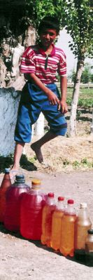 A boy sells smuggled fuel in Kyrgyz Republic, by-passing taxation