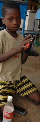 A boy cleans shoes in Burkina Faso. Child labour is a source of income and a symptom of poverty